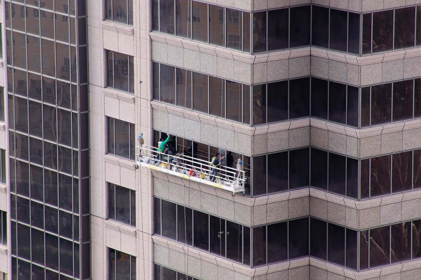 Presto technicians hang from swing stage outside high-rise office building to perform exterior glass, metal and stone restoration at 1100 Peachtree Street in Atlanta, GA