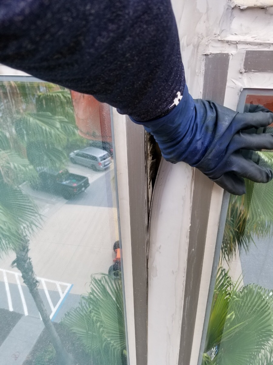 Presto technician inspecting failed caulking on office building