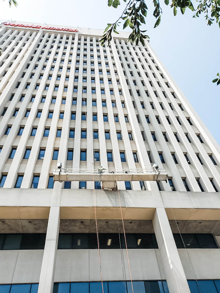 Presto waterproofing technicians suspended from swing stage on Reynolds American high-rise building in Winston-Salem, NC