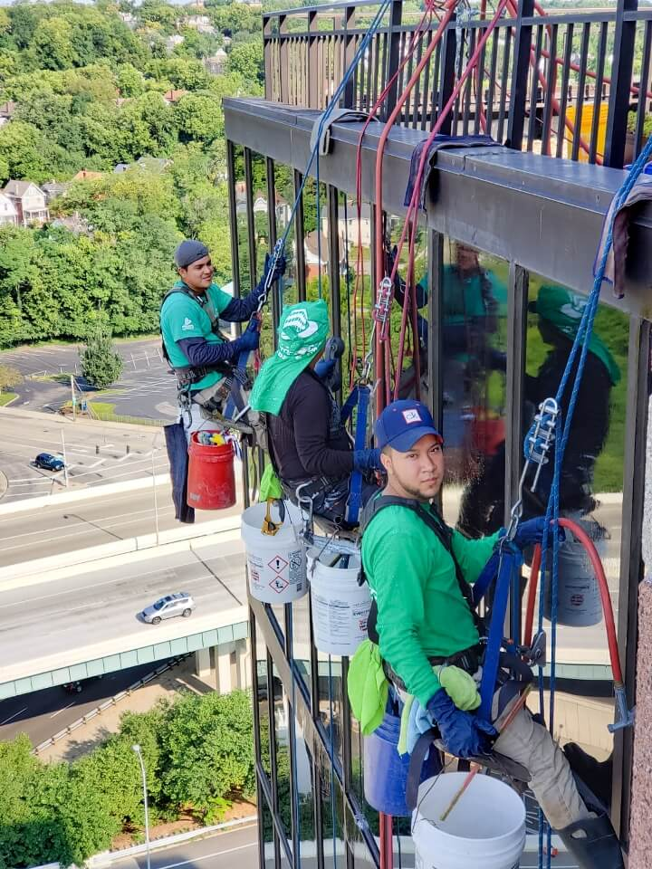 Presto technicians hanging on ropes performing glass restoration and waterproofing services on Cincinnati office building