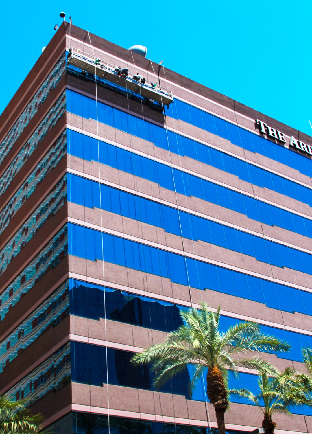 Presto techs on swing stage waterproofing the facade of a Phoenix, AZ high rise commercial office building