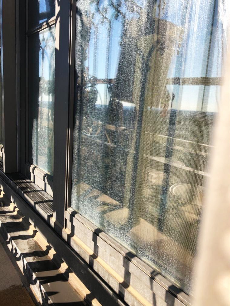 Hard water stains and streaks on windows of St. Regis hotel prior to Presto glass restoration