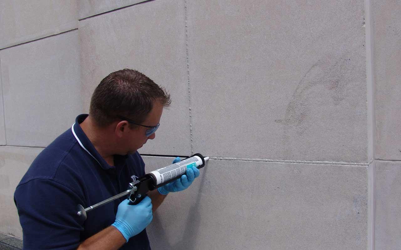 a presto technician caulking the exterior of a commercial building