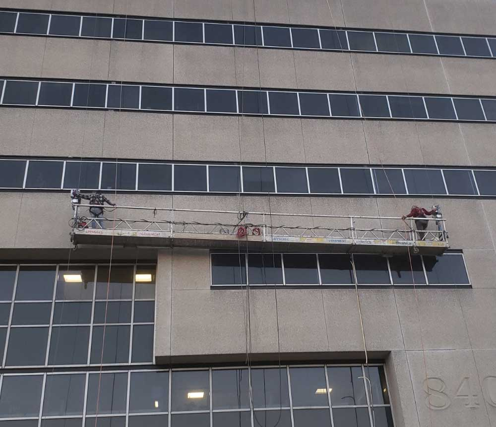 Presto crew using swing stage for office building restoration
