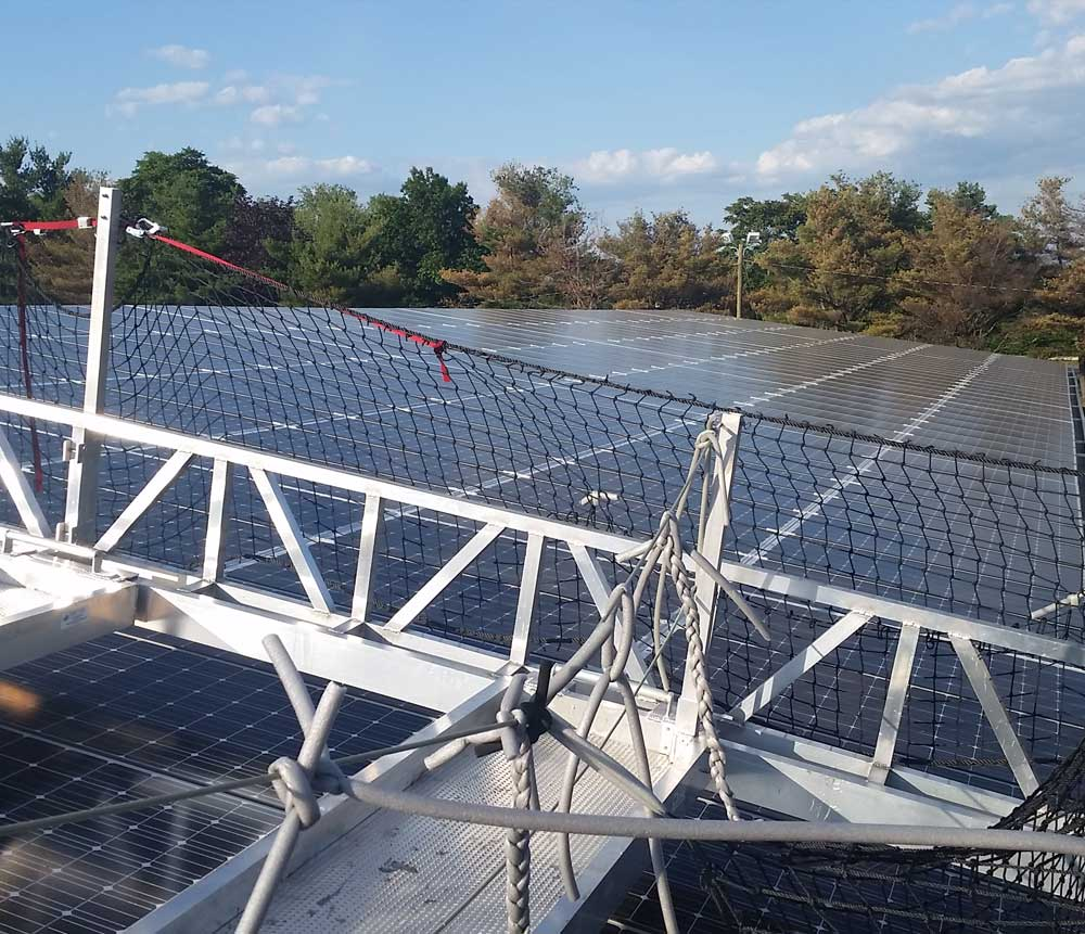 Presto technicians used scaffolding to safely apply caulking to solar panels without damaging them