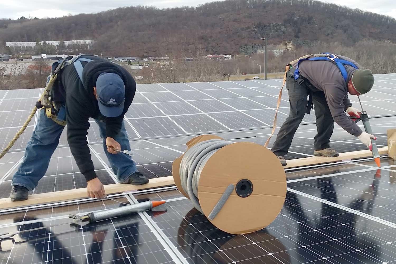 Presto technicians applying waterproofing solution to current solar panel installation
