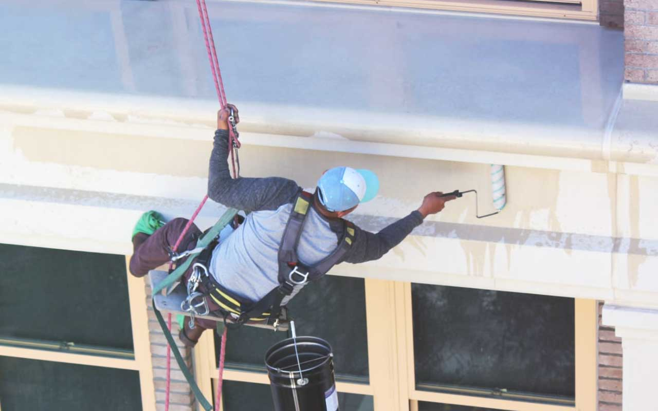 Waterproofing Expert Applying Coating to Exterior of Commercial Building