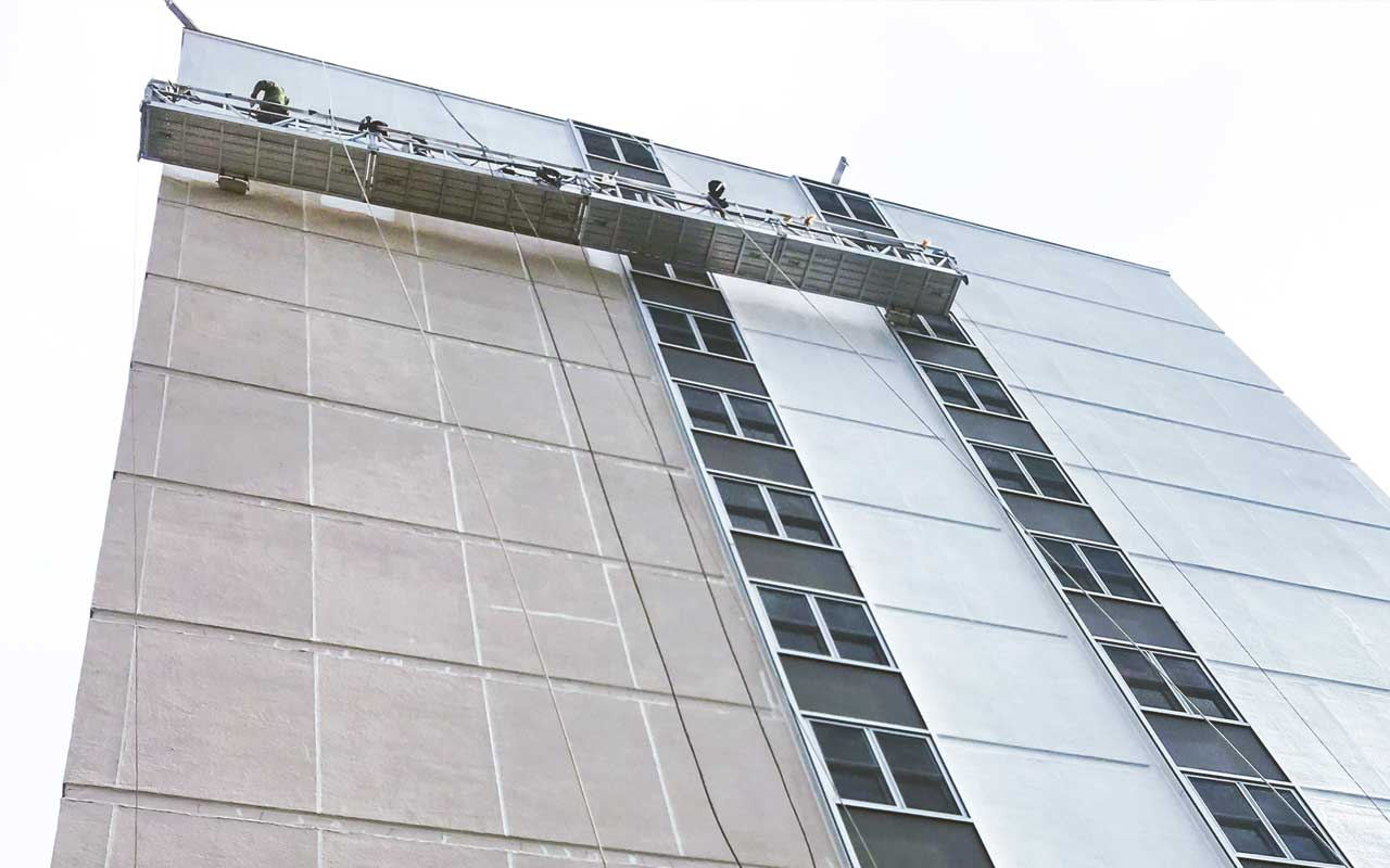 Presto applying an elastomeric coating to the EIFS of a commerical building