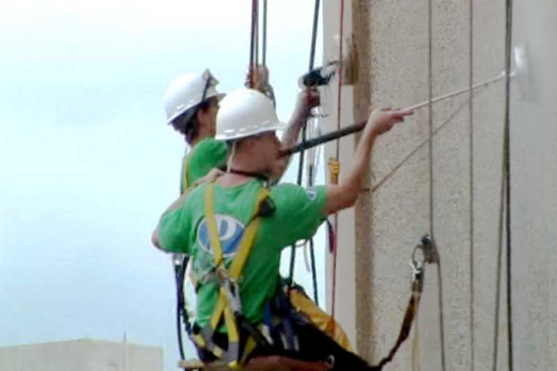 Using rappelling equipment to clean and seal an office building in West Virginia