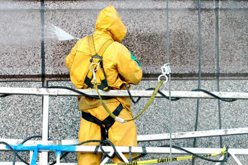 Prepping the exterior of an office building for sealing by cleaning with a sprayer