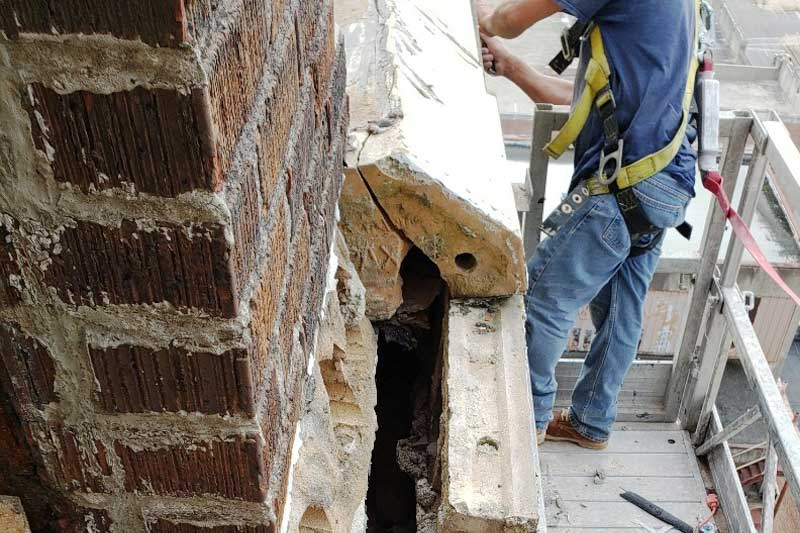 using a swing stage to perform masonry repairs on the Threefoot Building
