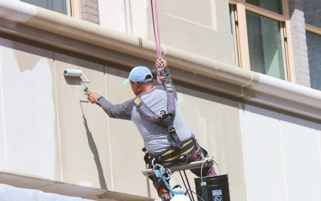 Commercial waterproofing company applying waterproofing coating to exterior of building
